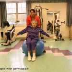 Older woman sitting on exercise ball with help from physical therapist
