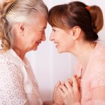old woman and middle aged woman holding hands, face to face and smiling