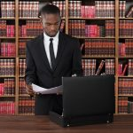Young African American male standing in a law library looking at paperwork