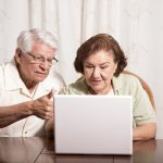 Older man and woman sitting at a table looking at a laptop