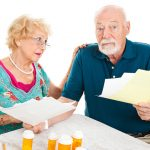 older man and woman sitting at a table looking over prescriptions and paperwork