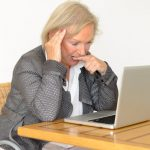 Older woman looking puzzled sitting in front of a laptop