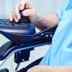 Elderly womans hand on the controls of an electric wheel chair