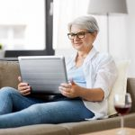 Grey haired woman with glasses, sitting on a couch with a laptop