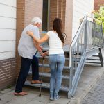 Young woman helping her elderly father up stairs