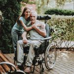 caregiving youth middle school girl hugging her dad in a wheelchair