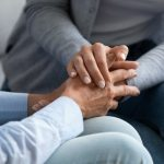 women hold hands for support
