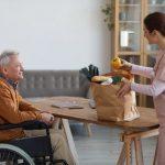 Aid helping a senior in a wheelchair