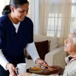 Home Care Aide providing dinner to an aging adult